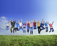 Verschiedene Menschen springen gleichzeitig vor blauem Himmel